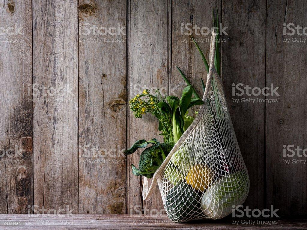 Légumes frais du marché suspendus dans un sac en coton réutilisable chaîne, sur un fond de mur vieille planche de bois. - Photo