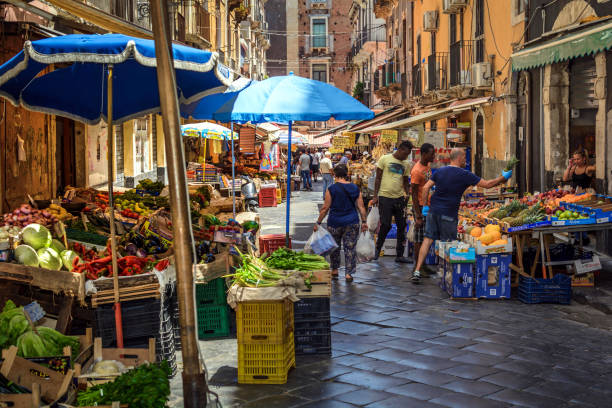 Market in Catania, Sicily Catania, Italy - July 2, 2018:  Fruit, vegetable and fish market in Catania runs everyday of the week right in the center of the city through the residential area. Many locals and tourists buying from the market traders. catania stock pictures, royalty-free photos & images