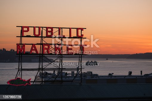 Seattle, USA - February 27, 2020: The famous neon public market sign at Pike Place Market with a Washington state ferry passing on Elliott bay at sunset.