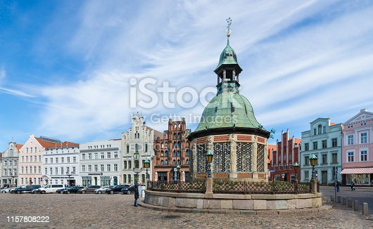 Wismar, Germany - May 15, 2019: The square's focal point is the Wasserkunst, an elaborate wrought-iron fountain imported from Holland in 1602.