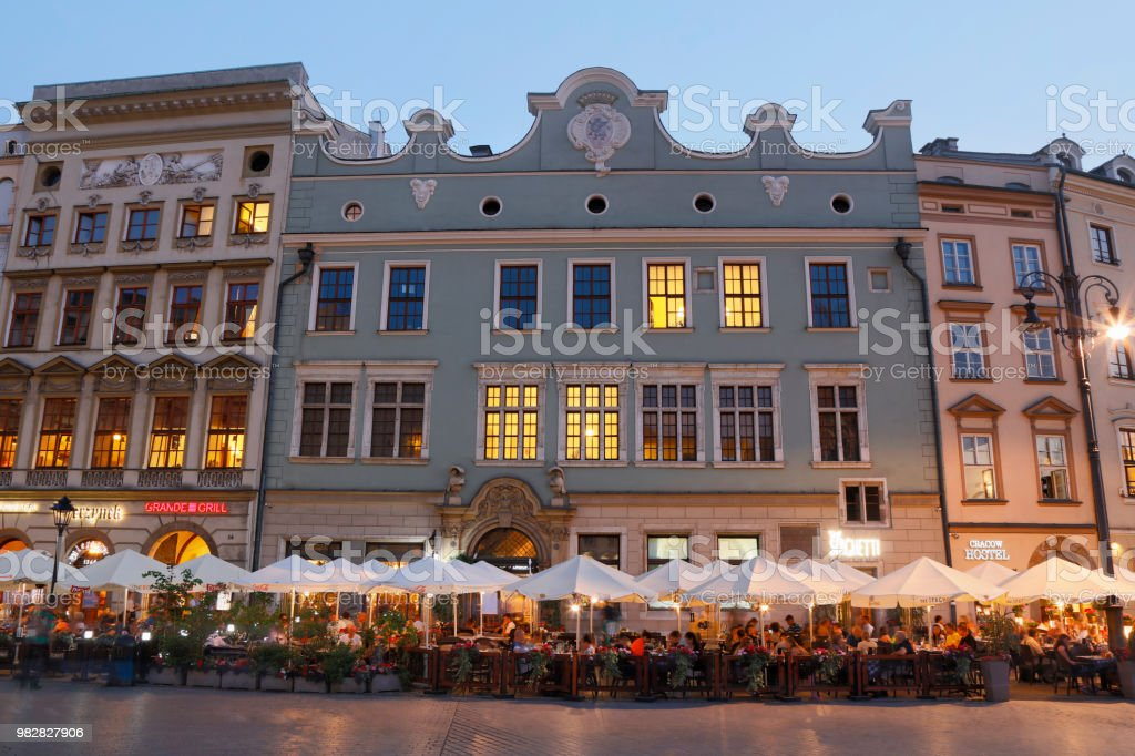 Market Square with street restaurants in Cracow at dusk. Crowds of...