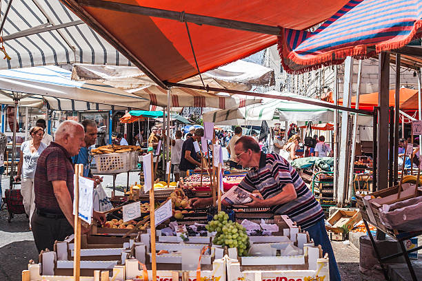 Market trader serves customers in a Palermo street, Sicily. stock photo