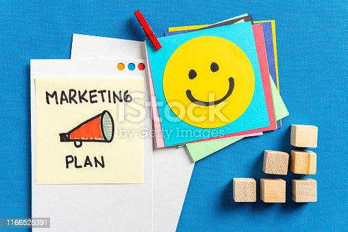 istock Marketing commercial advertising plan concept made with illustrated papers showing happy smiling face cartoon and still life wooden blocks and red clothespin, on blue textured background 1166525391
