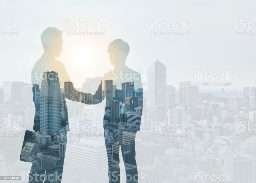 Marketing communication concept. Silhouette of business persons shaking hands. stock photo