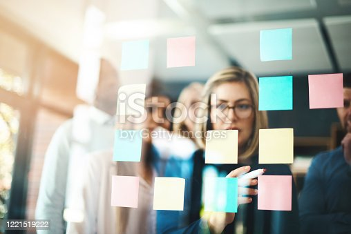 Shot of a group of businesspeople arranging sticky notes on a glass wall in a modern office