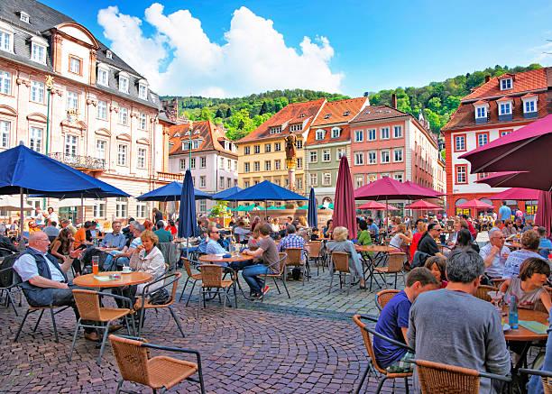 marktplatz übersät mit touristen und rathaus in heidelberg - sommerferien baden württemberg stock-fotos und bilder