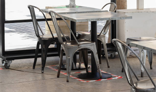 Marking on the ground and signage for physical or social distancing in bar or restaurant terraces stock photo