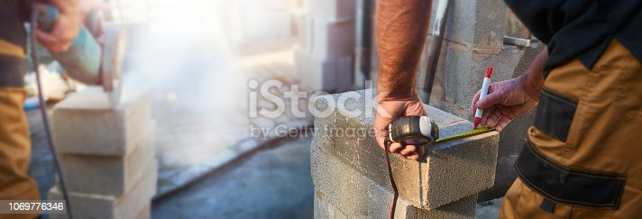 Building contractor measuring concrete block with tape measure and marking on guidelines to make his cuts with a marker pen while his colleague cuts the blocks to size