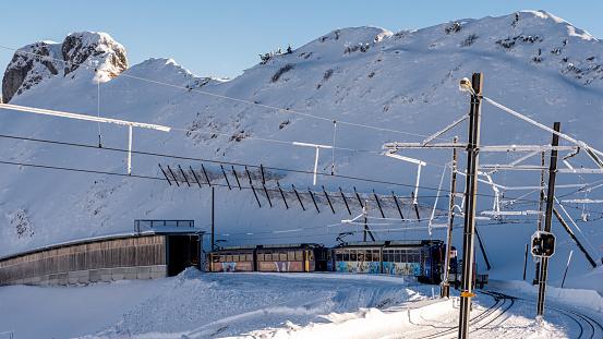 Marmots paradise cog railway train carriage leaving Rochers de Naye mountain summit stop in Switzerland in winter