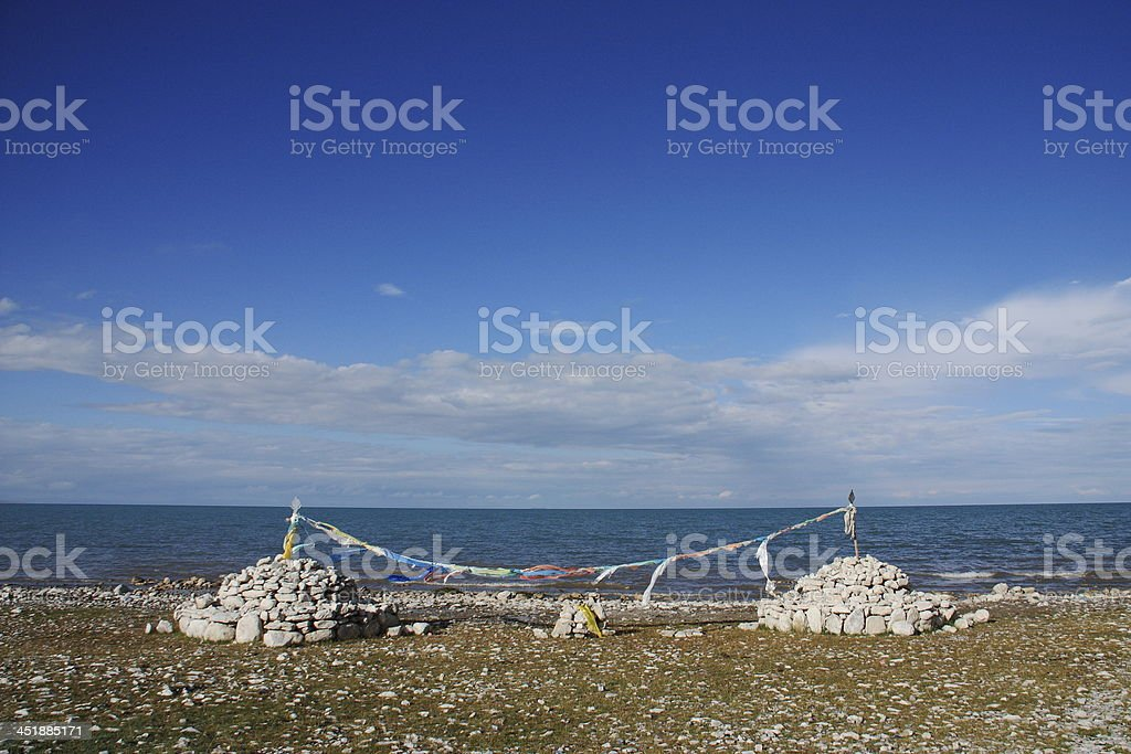 Marnyi Stone and Prayer flag nearby the Qinghai Lake royalty-free stock photo