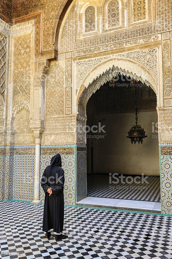 \'Maroccan man walking inside of Attarin Medersa. The Attarin Medersa...