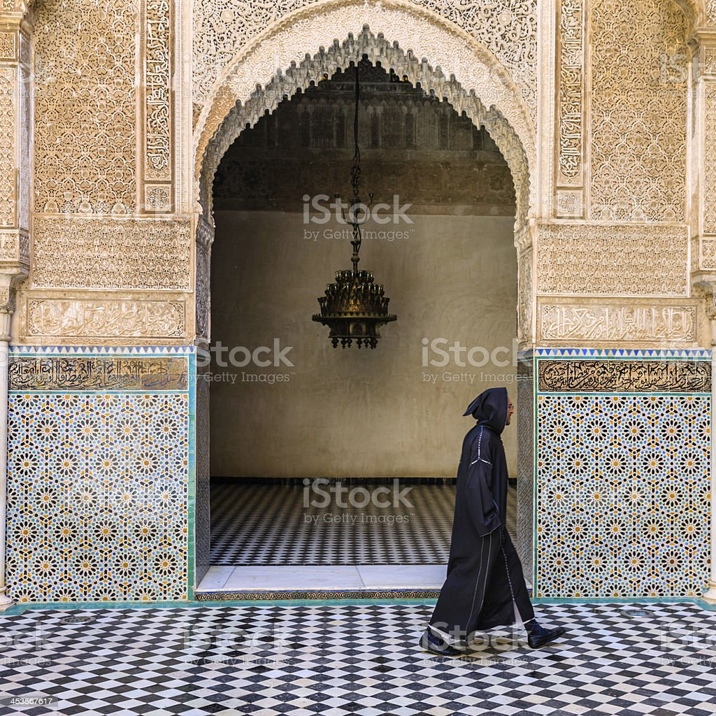 Maroccan man walking inside of Attarin Medersa in Fes, Morocco royalty-free stock photo