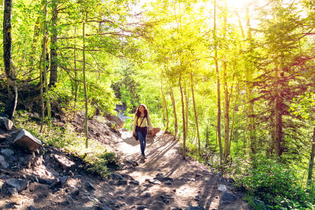 Maroon Bells Crater Lake hike with woman climbing steep dirt road in Aspen, Colorado in July 2019 summer stock photo