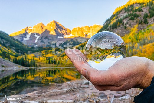 istock Maroon Bells lake at sunrise with hand holding crystal ball reflection in Aspen, Colorado with rocky mountain peak and snow in October 2019 autumn and vibrant trees 1213006987