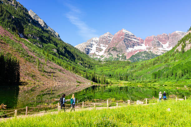 Maroon Bells lake in Colorado with tourist people in summer on trail path road wide angle view stock photo