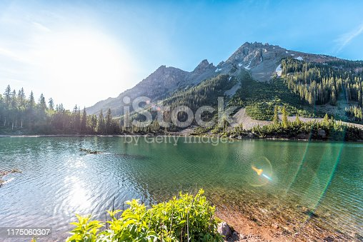 Maroon Bells rocky mountain snow peak view with Creater Lake in Colorado in summer wide angle view with bright sun and flare