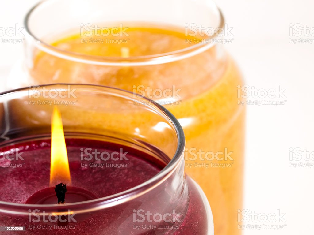 A maroon candle burning next to an orange candle not burning stock photo