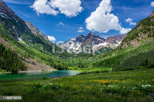 Majestic Maroon Bells peaks and Maroon Lake on a sunny day and blue sky in summer near Aspen, Colorado