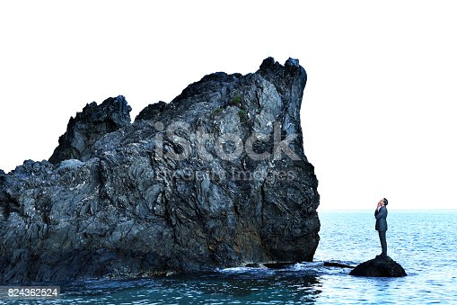A businessman stands marooned on top of a small rock in the ocean as he looks up to a much bigger rocky cliff that towers above him as he tries to figure out how to get there.