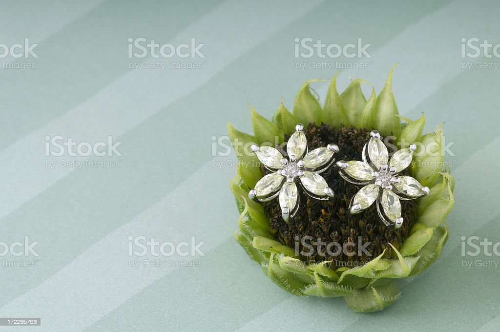 Marquise diamond earrings laying atop a floral accent royalty-free stock photo