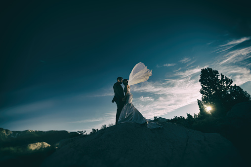 A couple embrace on a rock in the mountains with the wind blowing the bride's veil.