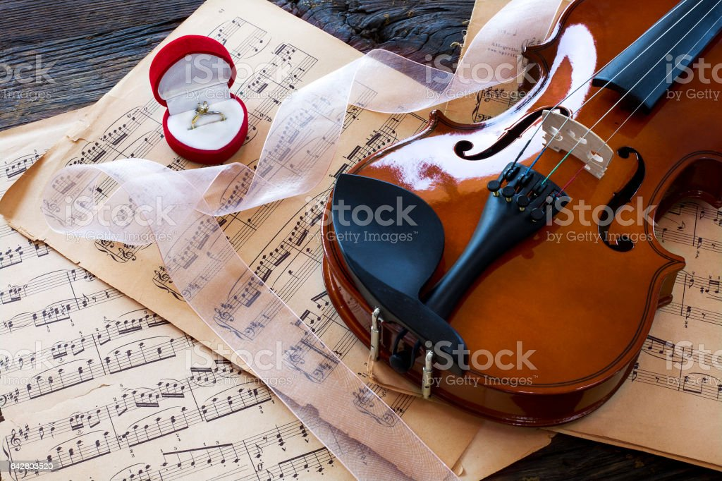 Marriage proposal with gold ring and violin on music notes stock photo