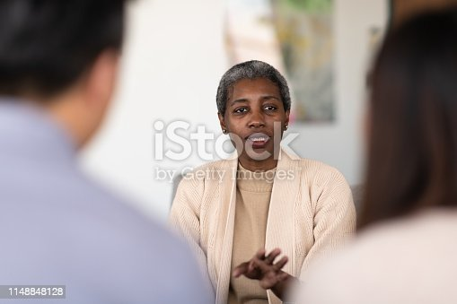 An elderly marriage counselor talks to her two patients about their struggles and obstacles. She is serious but optimistic that they can work through their problems.