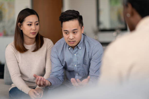 Marriage therapy An Asian married couple talks to a therapist together about their life. They are attentive and focused on making their marriage work. asian couple arguing stock pictures, royalty-free photos & images