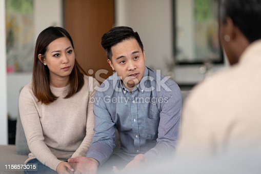 An Asian married couple talks to a therapist together about their life. They are attentive and focused on making their marriage work.