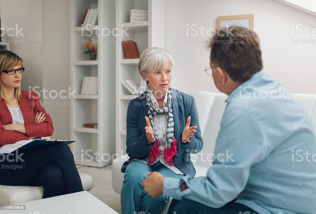 Marriage Therapy: Senior Couple Talking to Counselor stock photo