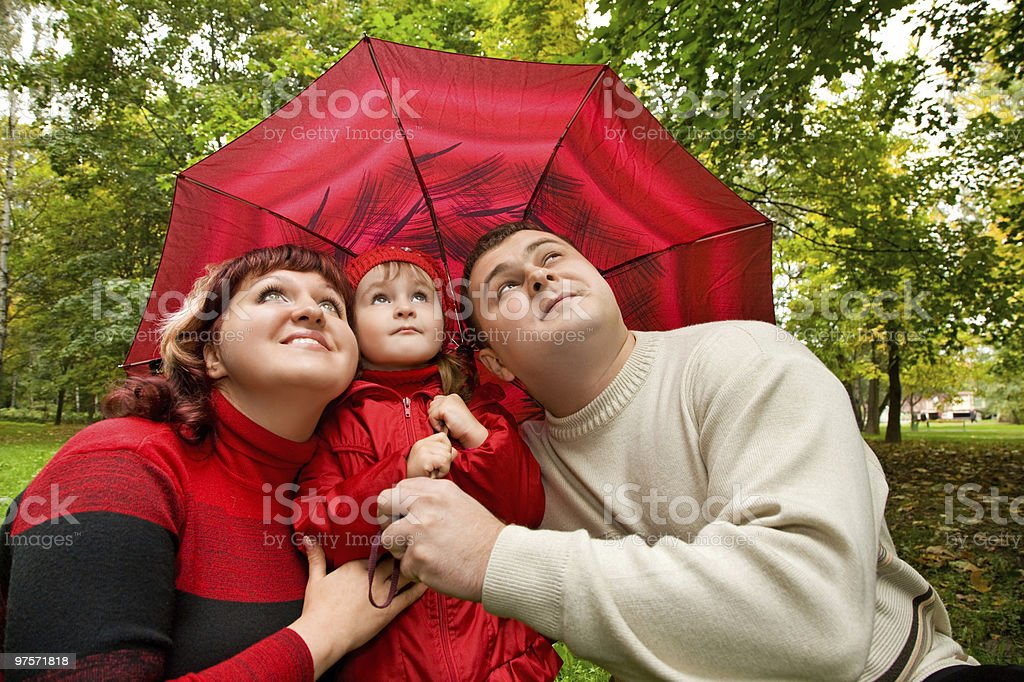 Married couple and little girl on an umbrella in park royalty-free stock photo
