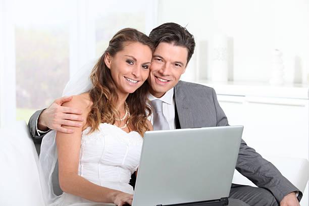 verheiratetes paar zu hause mit laptop-computer - hochzeitskleider online stock-fotos und bilder