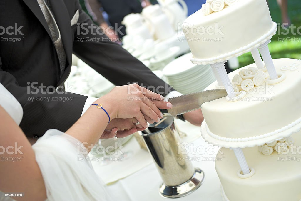 Married couple cutting their three layer cake stock photo