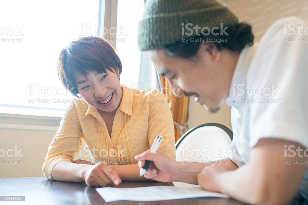 Married couple filling out paperwork together stock photo