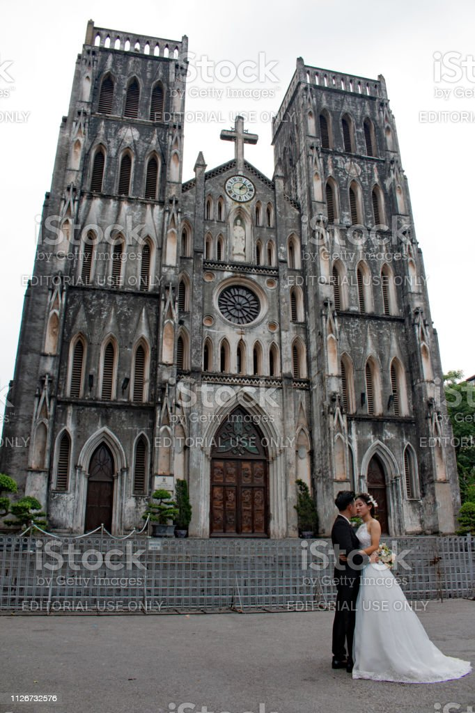 Married couple in front of St. Joseph's Cathedral, Hanoi stock photo