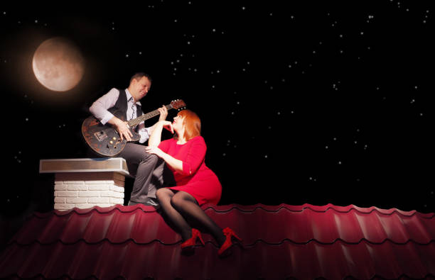 A married couple is sitting on the roof of a house at night. A married couple is sitting on the roof of a house at night serenading stock pictures, royalty-free photos & images
