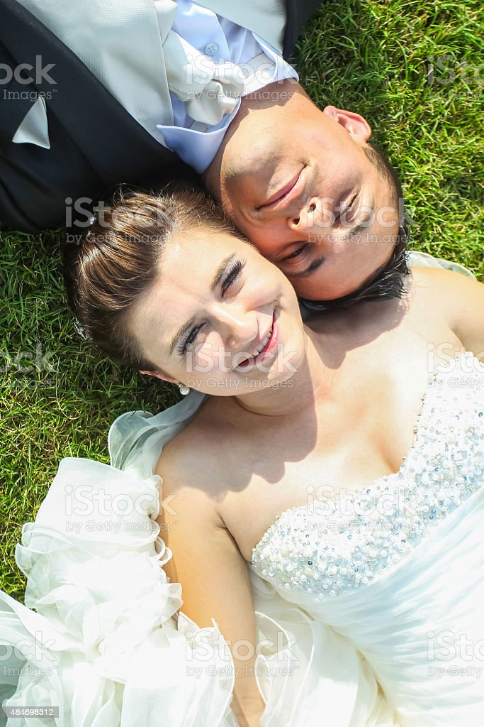 Married couple lying on grass stock photo
