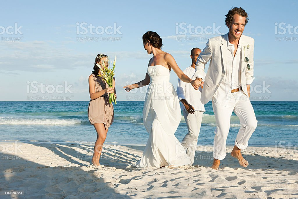 Married couple on beach with friends stock photo