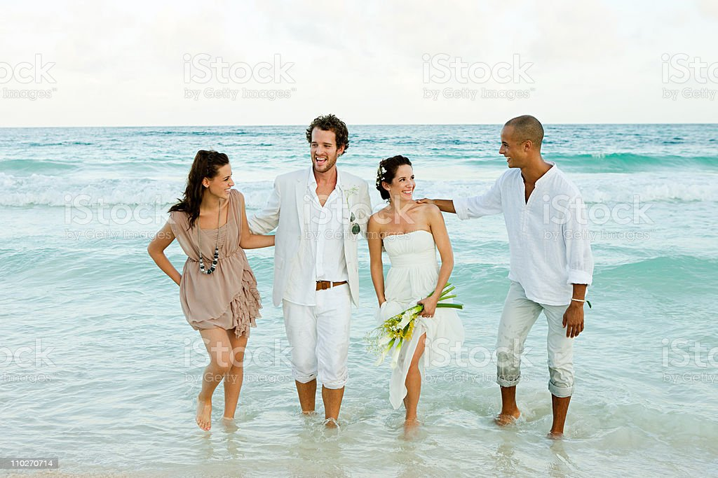 Married couple paddling in sea with friends royalty-free stock photo
