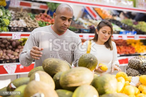 Married couple picking ripe melon at a grocery supermarket