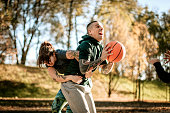 Young married couple playing basketball game on sport court, outdoor, fighting for ball