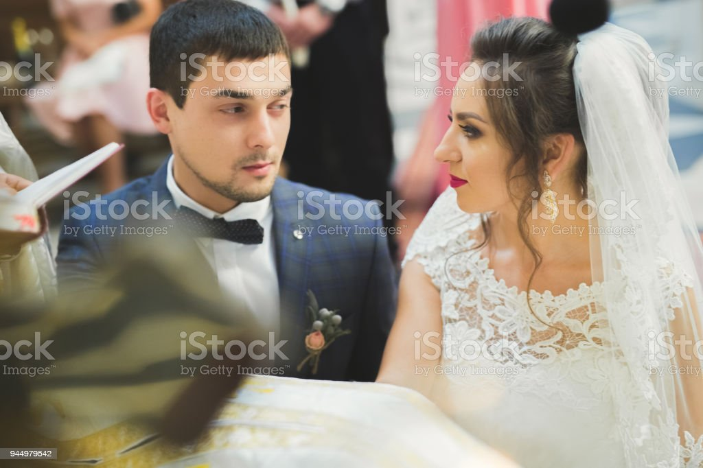 Married couple posing in a church after ceremony stock photo