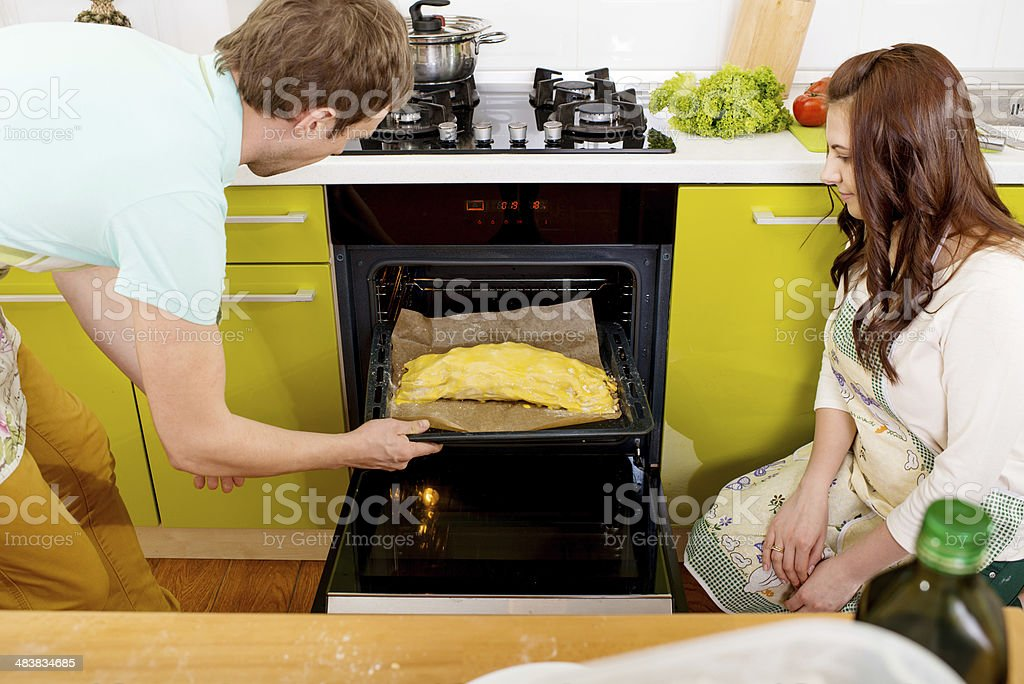 Married couple putting apple to oven in the kitchen royalty-free stock photo