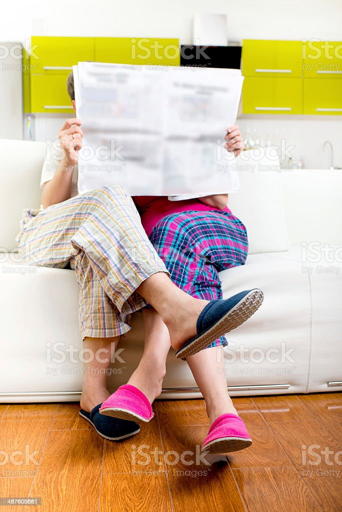 Married couple reading newspaper dressed in pajamas stock photo