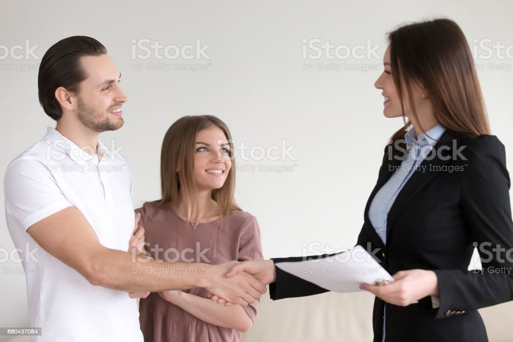 Married couple shaking hands with estate agent in new home stock photo