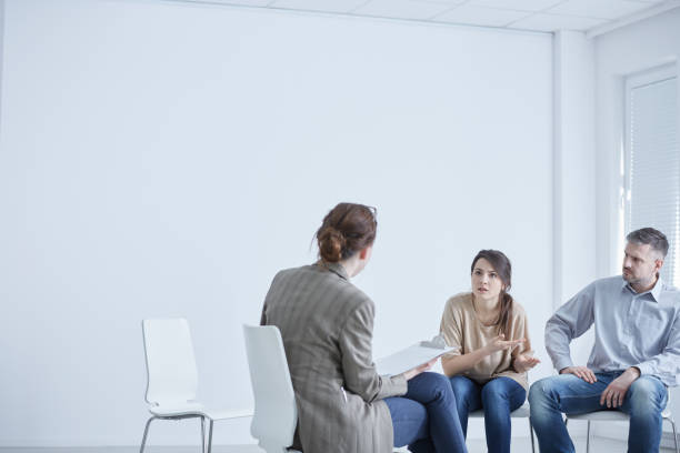 married couple talking with therapist - muscolo mentale foto e immagini stock
