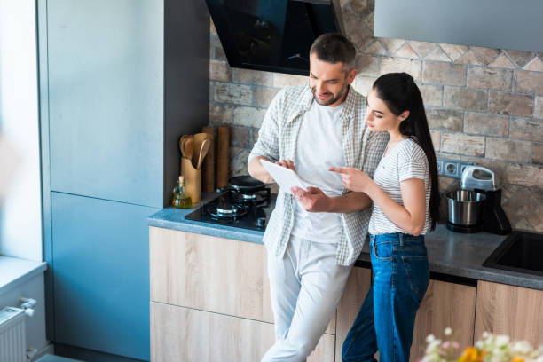 married couple using digital tablet together in kitchen, smart home concept married couple using digital tablet together in kitchen, smart home concept home automation stock pictures, royalty-free photos & images