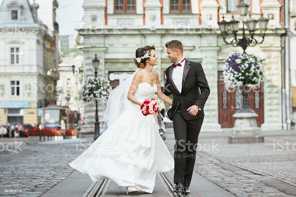 Married couple walking in the city and holding bouquet stock photo
