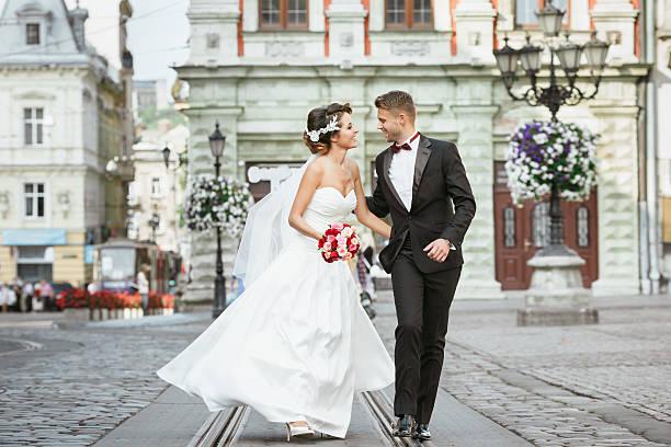 married couple walking in the city and holding bouquet - verlobungskleider stock-fotos und bilder