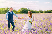 married couple walking in the field of purple flowers, the bride leads the groom behind her, the girl holds the guy by the hand, smiles, smoking hair, a woman in a white wedding dress, blue suit.
